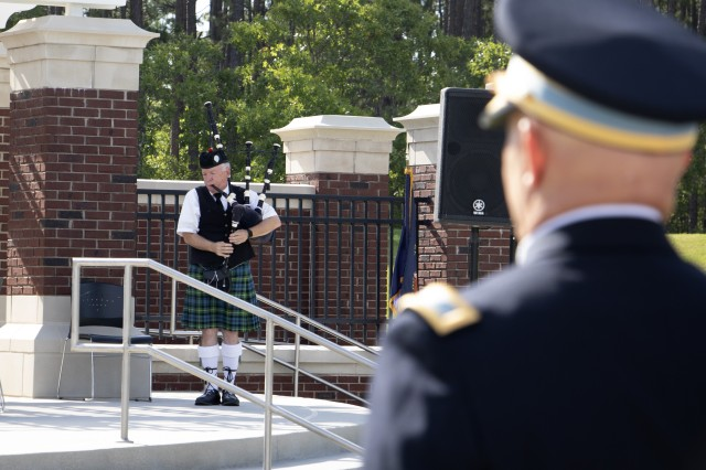 Glen Adams, a Scottish bagpiper, plays a solemn ballad during the wreath laying ceremony.