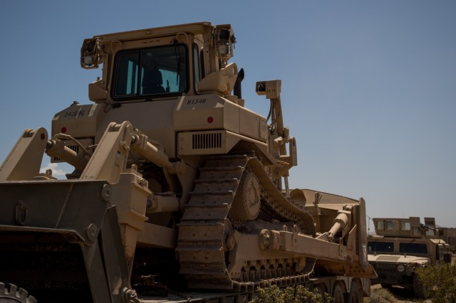 A D7 Dozer sit on a trailer park in the 242nd Engineer Company in the company's tactical assembly area June 1, 2019 at the National Training Center in Fort Irwin, California. The 242nd Engineer Company is one of two Kansas Army National Guard companies supporting the 116th Cavalry Brigade Combat Team's National Training Center rotation. Units from 13 Army National Guard states and territories are supporting the 116th CBCT's rotation May 24 through June 20. The rotation builds unit and Soldier proficiency to provide combatant commanders with a trained and ready force capable of fighting and winning our nation's wars.