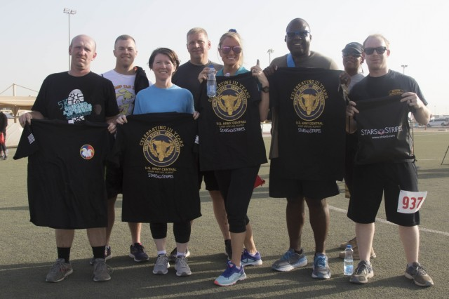 CAMP ARIFJAN, Kuwait - Soldiers with the 1st Theater Sustainment Command, show T-shirts they earned after participating in the Army Reserve's 111th birthday celebration 5K at Camp Arifjan, Kuwait, April 26, 2019. U.S. Army Central participates in events such as the birthday celebration to show commitment to the total force. (U.S. Army Reserve photo by Sgt. Christopher Lindborg, U.S. Army Central Public Affairs Office)