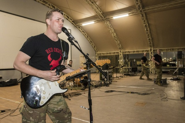 CAMP ARIJAN, Kuwait - Army Sgt. Christian Bueng, a musician with the Red Devil Rock Band, 34th Red Bull Infantry Division Band, Minnesota National Guard, performs cover songs on March 16, 2019, at Camp Arifjan, Kuwait. U.S. Army Central hosts these types of events to demonstrate its enduring commitment to Soldiers' health, welfare and morale. (U.S. Army Reserve photo by Sgt. Christopher Lindborg)