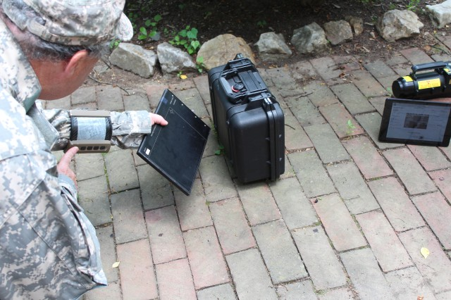 An explosive ordnance disposal Soldier wearing a future flexible wrist display unit, provided by Raytheon. The Soldier is using a digital detector array with flexible imaging and an X-ray generator to determine if there is explosive ordnance in the container.