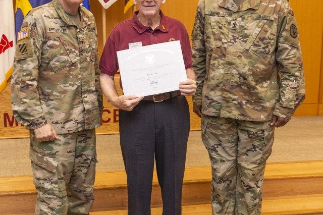 BAMC Commanding General Brig. Gen. George Appenzeller and Sergeant Maj. James Brown present Jerry Day, a ward clerk for the 2 North surgical intensive care unit, with the President's Lifetime Achievement Award on May 30, 2019 for his more than 12,000 service hours at Brooke Army Medical Center. Along with the presidential award, Day received the Commander's Award for Public Service for his many hours of selfless service.