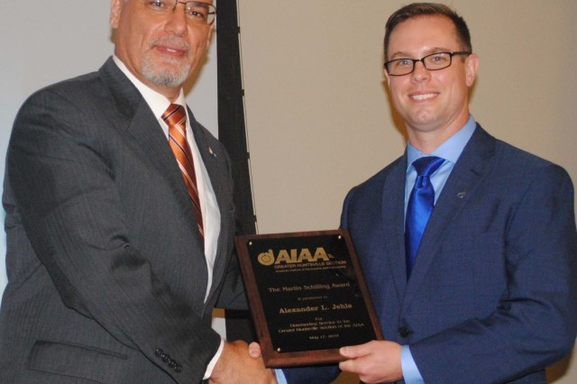 Maj. Alexander L. Jehle, right, principal investigator for the Space Systems Division of U.S. Army Space and Missile Defense Command/Army Forces Strategic Command Technical Center, receives the 2019 American Institute of Aeronautics and Astronautics Martin Schilling Award from Joe Majdalani, AIAA Honors and Awards director, at the society's 67th Annual Awards Dinner at the Jackson Center in Huntsville, Alabama May 17. Jehle served as the AIAA 2018-2019 chairman. (Courtesy photo)