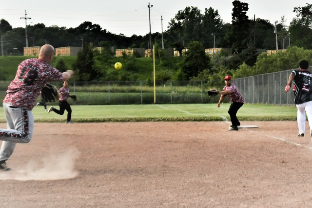 Human Resources Command pitcher Adam Pace attempts to throw out USAREC's Chris Pierson at first base during the Fort Knox intramural softball season opener at Kilianski Sports Complex June 4, 2019.
