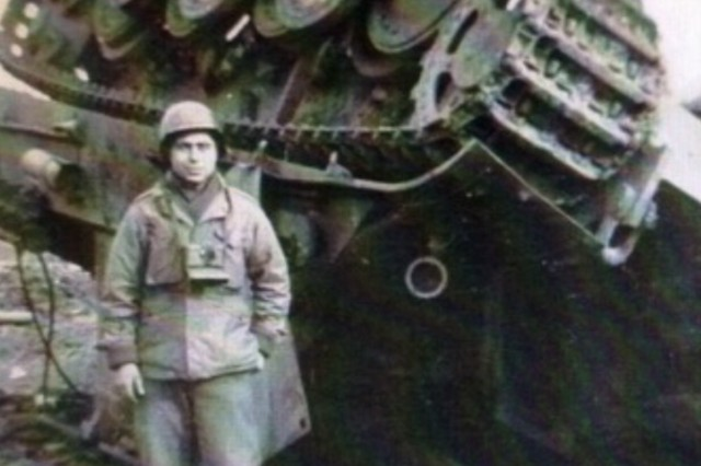 Cpl. Herman Zeitchik, 42nd Field Artillery, 4th Infantry Division, stands beside a destroyed tracked vehicle in Normandy, France, in 1944.