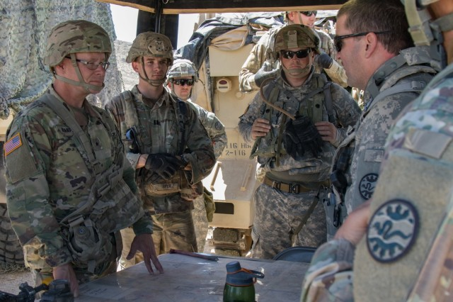 Idaho Army National Guard Capt. William Miller (far right), 3rd Battalion, 116th Cavalry Regiment intelligence officer, briefs Birg. Gen. Michael K. Hanifan, deputy commanding general, United States Army Intelligence Center of Excellence, on his battalion's fight against opposing forces at the National Training Center in Fort Irwin, California June 4, 2019. Hanifan visited the 116th Cavalry Brigade Combat Team's intelligence officers and sections to see firsthand how the Army's school for professional training of military intelligence prepares Soldiers to operate in a combat training center environment.