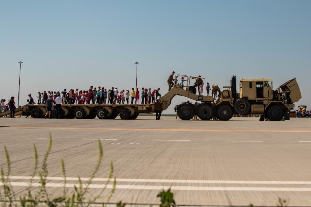 Students from local schools in Constanta, Romania wait their turn to climb through aM1070 Heavy Equipment Transport system during a field trip at the Mihail Kogalniceanu International Airport, Romania, May 29, 2019. The event hosted by US, Italian and Romanian Armed Forces gave the children a chance to see and interact with real military aircraft, vehicles and equipment and was also a good opportunity for military personnel to meet the locals. Many students were aided by U.S. Soldiers in order to traverse the machinery safely. (U.S. Army photo by Pvt. Laurie Ellen Schubert, 5th Mobile Public Affairs Detachment)