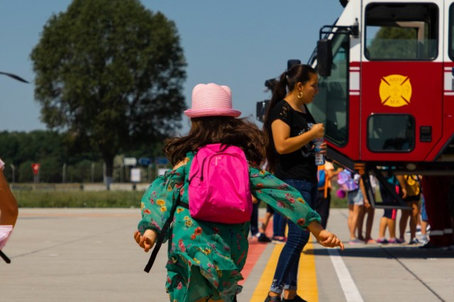 School children run from military vehicle to military vehicle at the Mihail Kogalniceanu International Airport, Romania, May 30, 2019. These students came from local schools during a field trip to meet and learn more about Romanian, Italian, and U.S. armed forces. (U.S. Army photo by Pvt. Laurie Ellen Schubert, 5th Mobile Public Affairs Detachment)