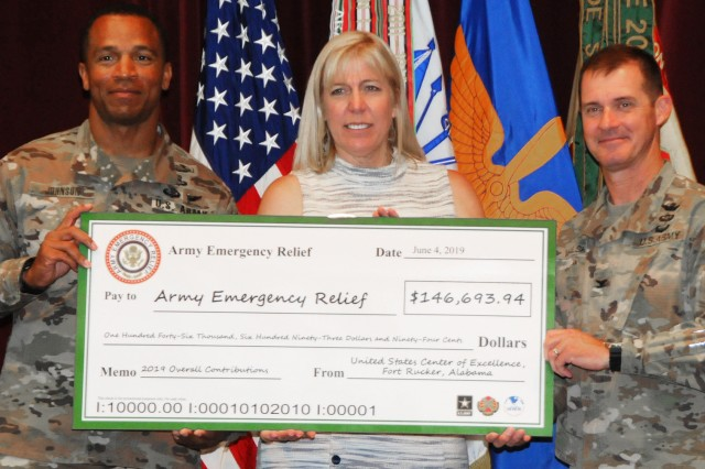 Col. Brian E. Walsh, Fort Rucker garrison commander, and Command Sgt. Maj. Jasper C. Johnson, garrison command sergeant major, present a symbolic check to Beth Gunter, Army Community Service financial counselor who works with AER at Fort Rucker, at the AER Awareness Campaign closing ceremony June 4 at The Landing.