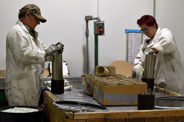 Blue Grass Army Depot staff re-prime the 105mm cartridge cases.
