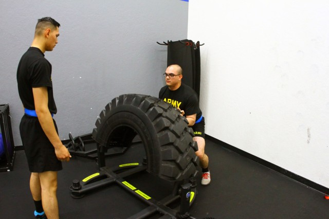 Pvt. Daniel Pacheco and Pfc. Bryan Buckberry, both of B Battery, 3-6th ADA, demonstrate 180-degree tire flip May 29, 2019, at the Honeycutt Gym and Functional Fitness Center.
