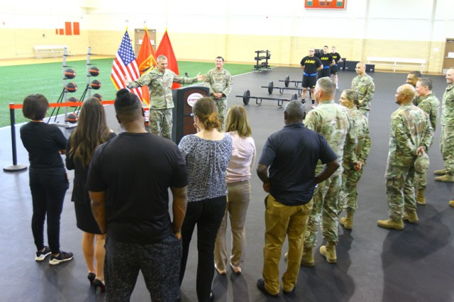 Ma. Gen. Wilson A. Shoffner (arms spread), Fires Center of Excellence and Fort Sill commanding general, speaks at the rededication of the Honeycutt Gym and Functional Fitness Center May 29, 2019. The center is set up so Soldiers can train on five of the new Army Combat Fitness Test six events, but not the 2-mile run.