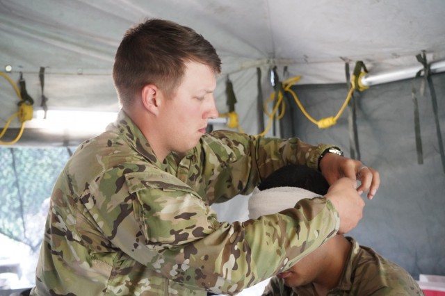U.S. Army Spc. Joshua Remy, 1st Squadron, 2d Cavalry Regiment places bandage around patient's head as part of a medical evacuation rehearsal during Saber Guardian 2019 at Várpalota, Hungary, June 3, 2019. 1/2CR is currently supporting SG19, an exercise co-led by the Romanian Land Forces and U.S. Army Europe that is taking place from June 3 - 24 at various locations in Bulgaria, Hungary and Romania. SG19 is designed to improve the integration of multinational combat forces. (U.S. Army photo by Sgt. LaShic Patterson)