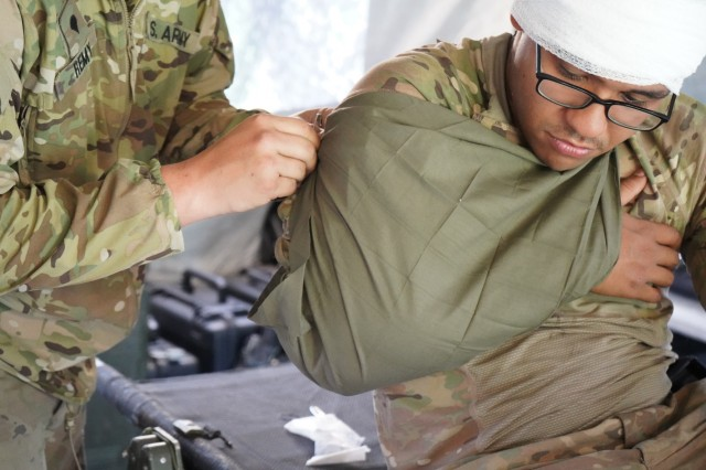U.S. Army Spc. Joshua Remy, 1st Squadron, 2d Cavalry Regiment pins a sling around a patient's shoulder as part of a medical evacuation rehearsal during Saber Guardian 2019 at Várpalota, Hungary, June 3, 2019. 1/2CR is currently supporting SG19, an exercise co-led by the Romanian Land Forces and U.S. Army Europe that is taking place from June 3 - 24 at various locations in Bulgaria, Hungary and Romania. SG19 is designed to improve the integration of multinational combat forces. (U.S. Army photo by Sgt. LaShic Patterson)