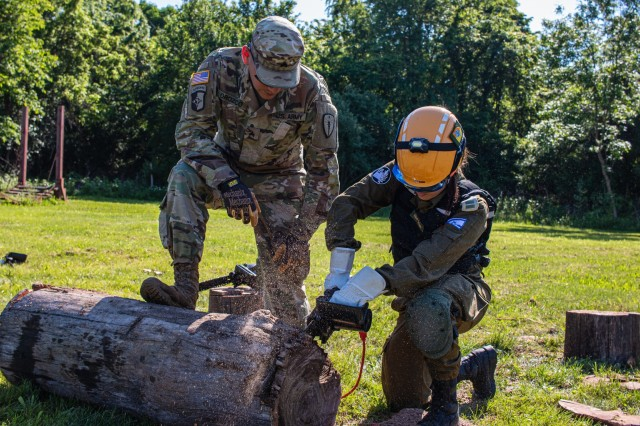 Army Sgt. Jeremy Orozco, a search and rescue squad leader from the 19th CERFP, guides an Israeli 1st Lt. Noa Cohen, IDF National Rescue Unit, in the application of a chainsaw during a round-robin training exercise for United Front VIII at Camp Atterbury May 31, 2019.