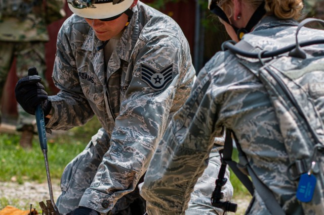 Airmen from the 19th CBRN Enhanced Response Force Package and hammer nails to make a shoring post during the round-robin training of the United Front VIII exercise at Camp Atterbury May 31, 2019. Shores are used to prop or support a weak or unstable tunnel during a search and rescue operation