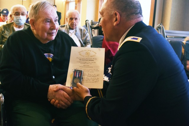 New York Army National Guard Col. Richard Goldenberg presents former Army Pfc. and World War II veteran Harry Myers with a New York State Medal of Merit at the 75th Anniversary of D-Day commemorative celebration at the Veterans' Home in Oxford, N.Y., on June 6th, 2019. The New York State Medal for Merit was presented to veterans of the allied invasion of Normandy during a statewide commemoration of the 75th anniversary of D-Day as part of an effort organized by New York Governor Andrew Cuomo. Ceremonies were held at five New York State Veterans Homes, with senior leaders of the New York National Guard participating to honor surviving World War II veterans and presenting 26 state medals.