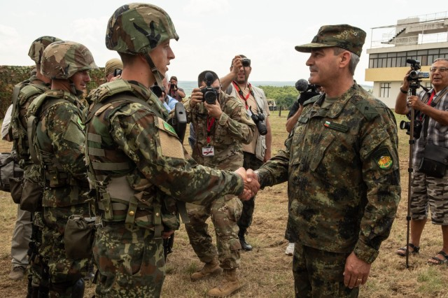 """Michigan Army National Guard Spc. Alan Prince, a public affairs specialist with the 126th Public Affairs Operations Center, captures the moment Brig. Gen. Kostadin Kuzmov, commander of the 2nd Mechanized Brigade, greets Bulgarian servicemembers during the opening ceremony of STRIKE BACK 19 held June 7, 2019 at Novo Selo Training Area, Bulgaria. """"The thousands of servicemen engaged in this exercise give an illustrious example of the aspirations of NATO and other partner states to build a peace and security in the Black Sea region,"""" said Kuzmov.(Photo by Michigan Army National Guard Spc. Samantha Hall)"""