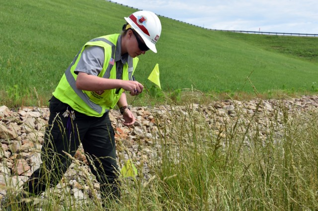Mallory Reynolds, U.S. Army Corps of Engineers, Tulsa District, park ranger at John Redmond Reservoir, near Burlington, Kansas, marks a location on the downstream side of the dam's embankment June 6. Reynolds is a part of a team that is monitoring the dam to ensure it continues to perform as designed. The Tulsa District is managing reservoirs across the region to reduce flood risks following historic rains in May in Kansas and Oklahoma.