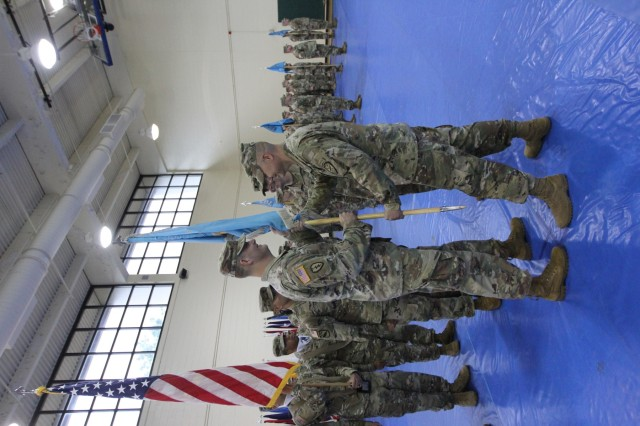 FORT GORDON, Ga. - Lt. Col. Wayne Sanders (left), the commander of the 782nd Military Intelligence (MI) Battalion (Cyber), accepts the battalion colors from Col. Brian Vile, commander of the 780th MI Brigade (Cyber), during a change of command ceremony at the Cyber Fitness Center on June 7.