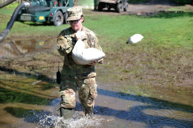 Spc. Kailey Bellville, a unit supply specialist in Headquarters Company, 1st Battalion, 279th Infantry Regiment, 45th Infantry Brigade Combat Team, Oklahoma Army National Guard, hauls sandbags to the base of a tree in the yard of Sand Springs, Oklahoma resident Bob Casebold, May 30, 2019. Oklahoma National Guardsmen are working alongside first responders and emergency personnel to provide disaster relief following record-breaking flooding of the Arkansas River in the Tulsa, Okla. area.