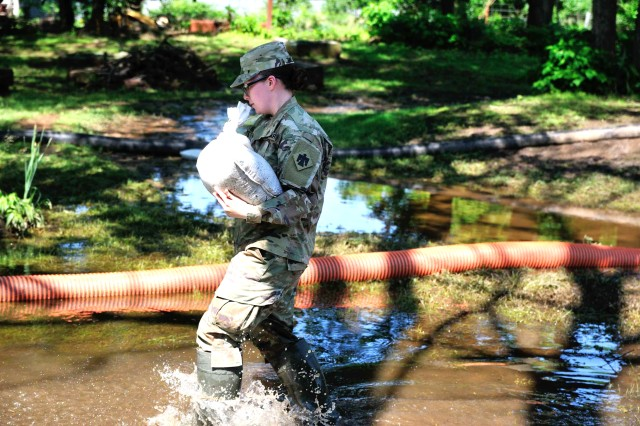 Spc. Kailey Bellville, a unit supply specialist in Headquarters Company, 1st Battalion, 279th Infantry Regiment, 45th Infantry Brigade Combat Team, Oklahoma Army National Guard, hauls sandbags to the base of a tree in the yard of Sand Springs, Oklahoma resident Bob Casebold, May 30, 2019. Oklahoma National Guardsmen are working alongside first-responders and emergency personnel to provide disaster relief following record-breaking flooding of the Arkansas River in the Tulsa, Okla. area.