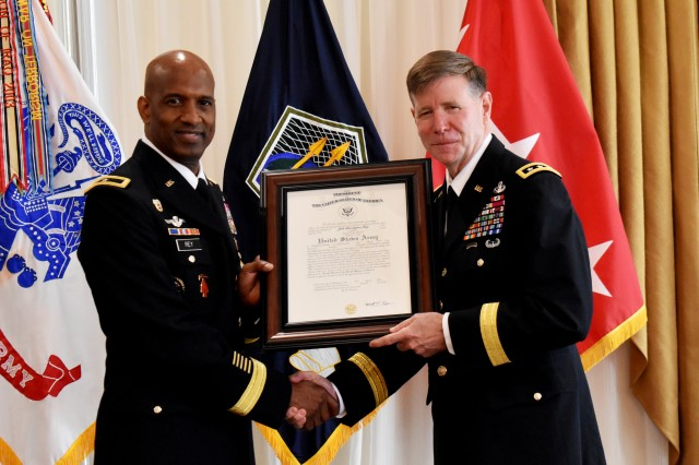 Lt. Gen. Stephen Fogarty (right), Army Cyber Command commanding general, presents newly promoted Brig. Gen. Jeth Rey, with his certificate of appointment during a ceremony June 3, 2019. Throughout his 35-year career, Rey has held a total of 16 ranks.