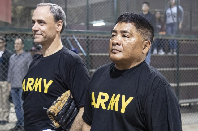 Capt. Noel Cronin and Sgt. Maj. Romeo Gamazon, leaders of the Every Soldier's an Ambassador effort, stand at attention during The National Anthem to commence an off-duty softball social event between service members of Task Force Spartan and the local Kuwaiti community on March 15, 2019 at the Hunting and Equestrian Club in Kuwait. The event brought people of all ages, nationality and gender, encouraging participation within the sport and local support for the activities. Soldiers are encouraged to develop a pathway for Community Outreach and Social Partnerships with Sporting Events as part of Every Soldier's an Ambassador program.