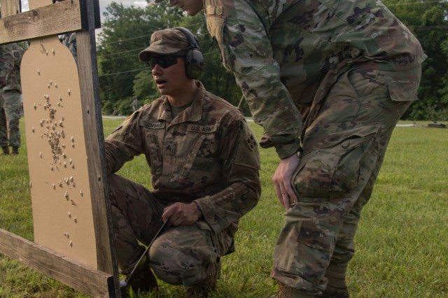 Cadet Matthew Clark from Ohio State University, and Sgt. Wesley Yellowwings check and assess Clark's target to help zero his weapon during Group and Zero training on May 31 at Fort Knox, Kentucky.