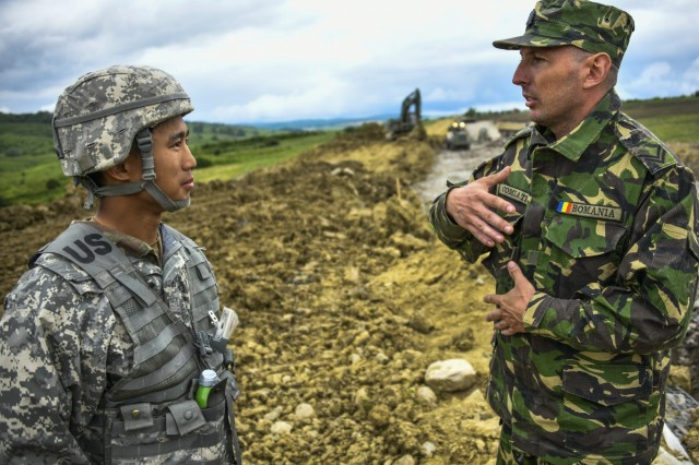 Vincent Owyong, a 2nd. Lt. from the 240th Engineer Company based in Las Vegas, Nevada, speaks with a soldier from the Romanian Land Forces (who chooses to be unnamed) during a construction project in Cincu, Romania, May 31st, 2019. The project is part of exercise Resolute Castle 2019, a multi-national joint exercise with real-world outputs of completed construction projects that build and enhance training capabilities around Eastern Europe.