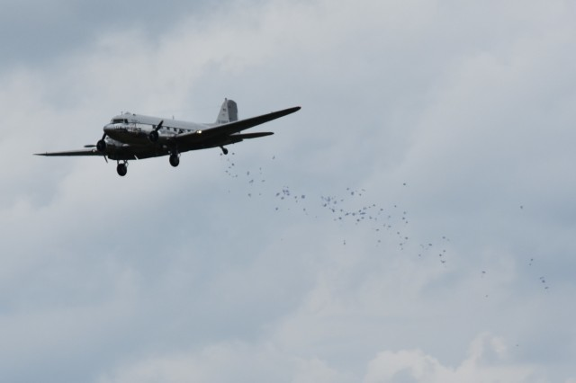 """A C-47 Skytrain drops mini parachutes attached to candy to children waiting below June 10, 2019, on the U.S. Army Garrison Wiesbaden airfield at Clay Kaserne. The candy drop, which was reminiscent of drops made in 1948 and 1949 by then U.S. Air Force Lt. Gail Halvorsen, known as the """"Candy Bomber"""" was a part of the Berlin Airlift 70th Anniversary Commemoration. (U.S. Army photo by Jessica Ryan)"""