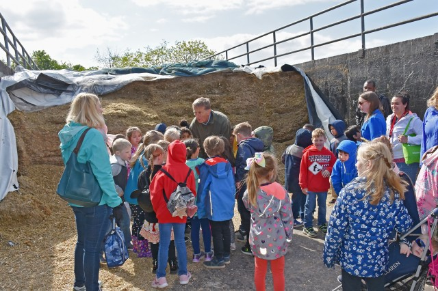 Horst Freund, chief of the department of fruits and vegetables at Domäne, explains to the students what silage is. It is a fermented food for the cows. The first-graders visited the organic farm next to Clay Kaserne May 3, 2019, as part of Earth Day activities organized by the U.S. Army Garrison Wiesbaden Environmental Division.