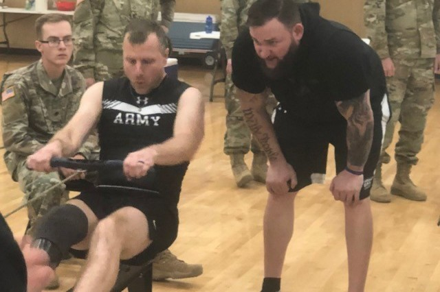 Retired U.S. Army Staff Sgt. Ross Alewine (right) stands beside retired U.S. Army Capt. Tim Bomke giving him words of encouragement during the rowing competition at Army Trials in Fort Bliss, Texas - March 7, 2019. (Photo courtesy MaryTherese Griffin, Warrior Care and Transition)