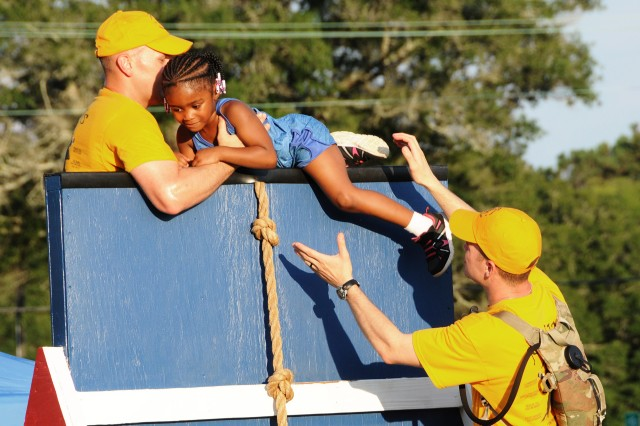 Soldiers from the U.S. Army Warrant Officer Career College help a child navigate through the children's obstacle course at last year's event.
