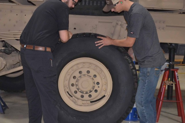Austin Prestwood, left, and Brandon Carr attach a tire to the M8E1 CBPS.