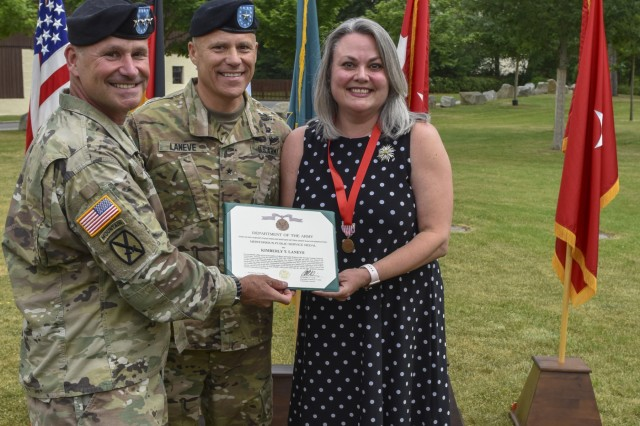 U.S. Army Lt. Gen. Christopher Cavoli, commander of U.S. Army Europe, Brig. Gen. Christopher LaNeve, commander of  7th Army Training Command (7th ATC), and his wife, Kimberly, pose for a photo as she  receives the Meritorious Public Service Medal from Cavoli at 7th ATC headquarters at Tower Barracks, Germany, June 11, 2019. Immediately following was the 7th ATC Change of Command. (U.S. Army photo by Sgt. Christopher Stewart)