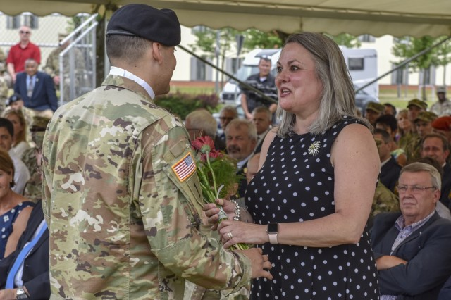U.S. Army Sgt. Kyle Lameli presents Kimberly LaNeve, wife of Brig. Gen. Christopher LaNeve, outgoing commander of 7th Army Training Command (7th ATC), during a Change of Command ceremony on the parade field at Tower Barracks, Germany, June 11, 2019. The Change of Command ceremony represents the passage of command from LaNeve to Brig. Gen. Christopher R. Norrie, incoming 7th ATC commander. (U.S. Army photo by Sgt. Christopher Stewart)