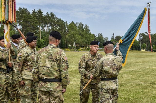 U.S. Army Brig. Gen. Christopher C. LaNeve, outgoing commander of 7th Army Training Command (7th ATC), passes the 7th ATC colors to Lt. Gen. Christopher G. Cavoli, commander of U.S. Army Europe, during a Change of Command ceremony on the parade field at Tower Barracks, Germany, June 11, 2019. The Change of Command ceremony represents the passage of command from LaNeve to Brig. Gen. Christopher R. Norrie, the incoming 7th ATC commander. (U.S. Army photo by Sgt. Christopher Stewart)