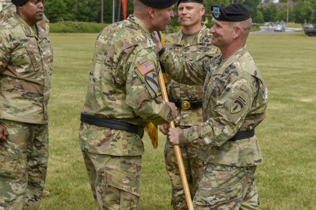 U.S. Army Lt. Gen. Christopher G. Cavoli, commander of U.S. Army Europe, passes the 7th Army Training Command (7th ATC) colors to Brig. Gen. Christopher R. Norrie, incoming commander of 7th ATC, during a Change of Command ceremony on the parade field at Tower Barracks, Germany, June 11, 2019. The Change of Command ceremony represents the passage of command from LaNeve to Norrie. (U.S. Army photo by Sgt. Christopher Stewart)