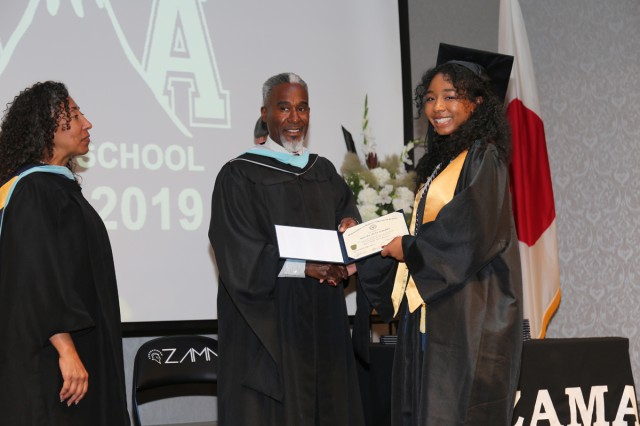 Matrika Franklin, the salutatorian for the Zama American High School graduating class of 2019, receives her diploma from ZAHS Principal Wayne Carter during the commencement ceremony June 6 at the Camp Zama Community Club.