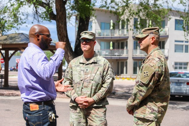 Jerome Ford, left, program director for Crawford House, U.S. Army Lt. Col. Timothy Palmer, middle, commander of 1st Battalion, 12th Infantry Regiment, 2nd Infantry Brigade Combat Team, 4th Infantry Division, and U.S. Army Sgt. Maj. Marcus Kremer, senior enlisted leader for 1st Bn., 12th Inf. Reg., 2IBCT, talk about the purpose of the Crawford House, May 17, 2019, in Colorado Springs, Colorado. Soldiers from 1st Bn., 12th Inf. Reg., 2IBCT, conducted a golf tournament to help gather items to donate to the support center. (U.S. Army photo by Staff Sgt. Neysa Canfield)