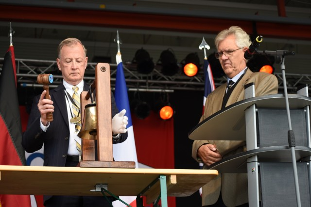 Bradley Provancha, the master of ceremonies, rings a bell 81 times to honor personnel who lost their lives during the Berlin Airlift as Dr. John Provan, local historian, looks on during a memorial service June 10, 2019, at Lucius D. Clay Kaserne airfield in Wiesbaden, Germany. The event commemorated those who participated in the historic military operation in 1948 to 1949. (U.S. Army photo by Jessica Ryan)