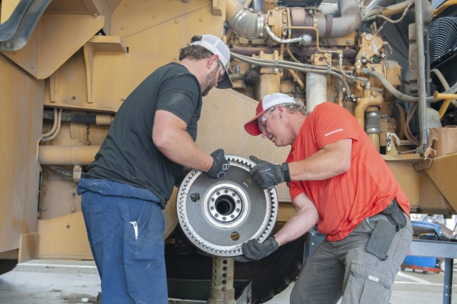 Brad Orman, left, and Bronson Vice assemble a planetary gear set for a hub assembly on a tow motor in Anniston Army Depot's Mobile Equipment Branch.