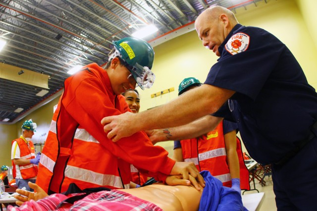 """Fort Sill Fire Station No. 3 Chief Michael Hickman (right),  shows Felipe Faria, 13, of MacArthur Middle School, how to lock his elbows as her performs CPR to the beat of the song """"Baby Shark"""" during the Community Emergency Response Team training June 5, 2019."""
