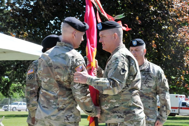 Lt. Col. Eric Schilling, left, receives the Iowa Army Ammunition Plant colors from Col. Michael Garlington, right, Crane Army Ammunition Activity commander, during the IAAAP Change of Command Ceremony, June 13. Outgoing commander, Lt. Col. Stephen Koehler, watches the transfer of authority.