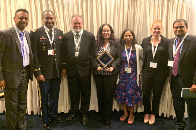 The U.S. Army Medical Materiel Agency earned a FedHealth IT Innovation 2019 Award on June 11, 2019, for a Blockchain initiative project supported by IndraSoft team. From left to right: Karthik Srinivasan, Col. Darryl McGuire, Eric Strattan, Liz Andrews, Hiral Patel, Nicole Hamlin, and Raj Lingam.