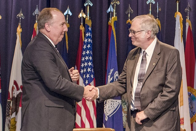 Brian E. Fuchs was named Senior Research Scientist for Insensitive Munitions at an appointment ceremony on June 10 at Picatinny Arsenal. At left, he is being congratulated by John Hedderich, Director of the Combat Capabilities Development Command Armaments Center. Insensitive Munitions are designed to be less susceptible to accidental detonation.