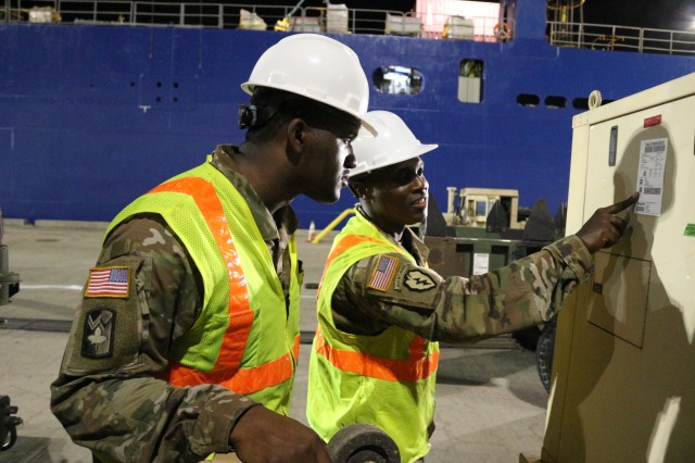 From left: Sgt. Dontre Austin and Staff Sgt. Andre Carroll, 599th operations NCOs, talk over information on a generator's shipping label during nighttime port operations on the M/V Ocean Jazz at Pearl Harbor on June 7.