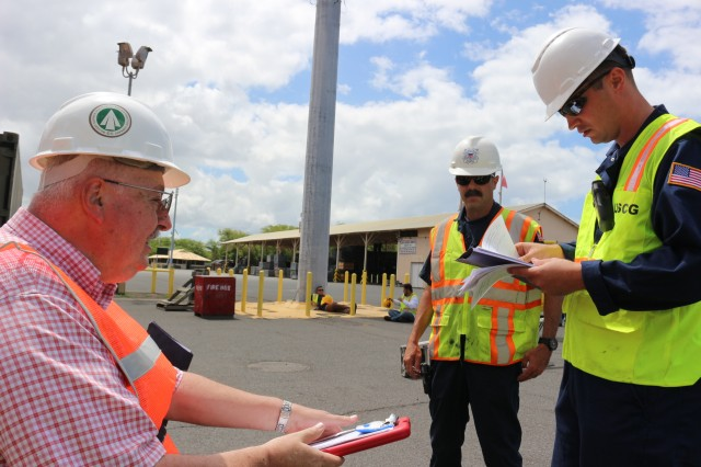 Carlos Tibbetts, 599th terminal operations chief, goes over paperwork with Coast Guard Petty Officers 1st Class Scott Thomas and 2nd Class Bret Reel during port operations on the M/V Ocean Jazz at NAVMAG Pearl Harbor on June 9.