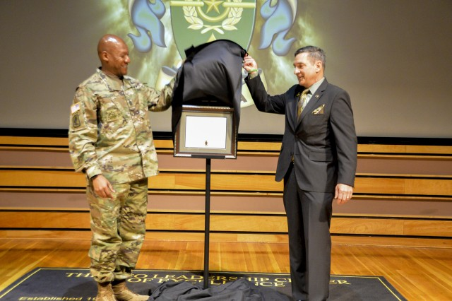 Command Sgt. Maj. Jimmy Sellers (left) the commandant of the NCO Leadership Center Excellence and former Combined Arms Center, retired Command Sgt. Maj. Philip Johndrow (right) unveil the United States Army Sergeants Major Academy, Bachelor of Arts in Leadership and Workforce Development diploma at the Kenneth W. Cooper Lecture Center on Fort Bliss, Texas, June 14 .